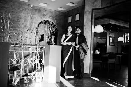 Foto de Lovely indian couple in love, wear at saree and elegant suit, posed on restaurant. - Imagen libre de derechos