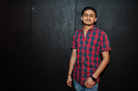 Photo for Asian man in checkered shirt against dark background. - Royalty Free Image