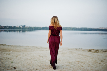 Photo for Back of blonde sensual barefoot woman in red marsala dress posing against lake. - Royalty Free Image