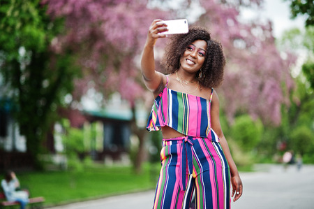 Fashionable african american woman in pink striped jumpsuit posed at spring bloom street and making selfie by mobile phone.
