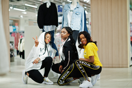 Foto per Three afican american women in tracksuits shopping at sportswear mall against mannequin. Sport store theme. - Immagine Royalty Free