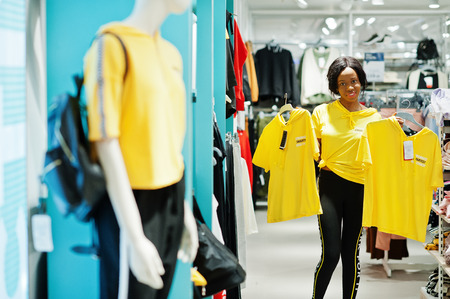 Foto per Afican american woman in tracksuits and sunglasses shopping at sportswear mall against shelves. She choose  yellow t-shirt. Sport store theme. - Immagine Royalty Free