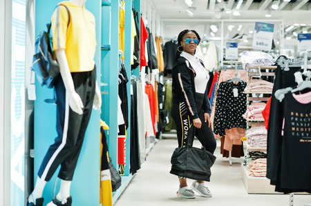 Foto per Afican american woman in tracksuits and sunglasses shopping at sportswear mall with sport bag against shelves. Sport store theme. - Immagine Royalty Free