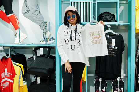 Foto per Afican american woman in tracksuits and sunglasses shopping at sportswear mall against shelves. Sport store theme. She hold top clothes. - Immagine Royalty Free