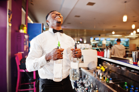 Photo for African american bartender at bar with two bottles. Alcoholic beverage preparation. - Royalty Free Image