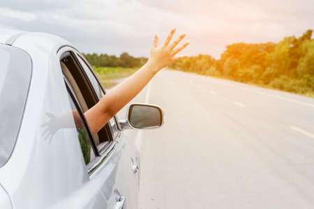 Photo pour Woman hand in the car relaxing and happy traveler on the road - image libre de droit