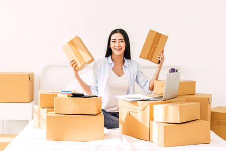 Foto de Young woman freelancer working and holding cardboard box on bed at home - SME business online and delivery concept - Imagen libre de derechos