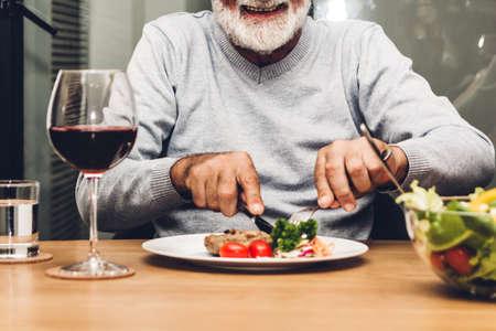 Foto für Happy senior man eating pork steak on table at restaurant - Lizenzfreies Bild