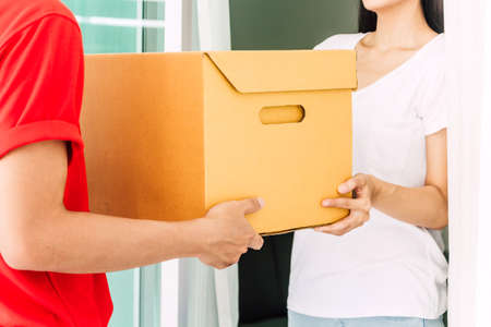 Photo for Woman accepting a delivery boxes from delivery man in red uniform.courier service concept - Royalty Free Image