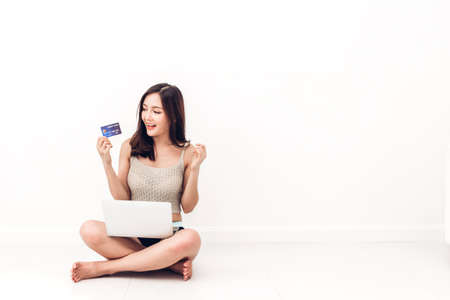 Foto de Beautiful woman shopping online with technology of laptop computer and credit card sitting on the floor against copy space for adding text with white wall background - Imagen libre de derechos