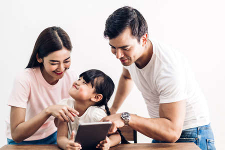 Photo pour Happy family father and mother with daughter sitting and looking at tablet computer together in the living room at home - image libre de droit