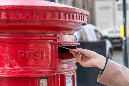 Foto de Throwing a letter in a red British post box from the side - Imagen libre de derechos