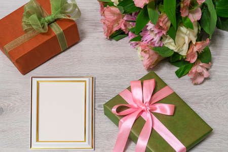 Photo for Colorful bouquet of roses, chrysanthemum and alstroemeria flowers with gift boxes and empty photoframe on wooden background - Royalty Free Image