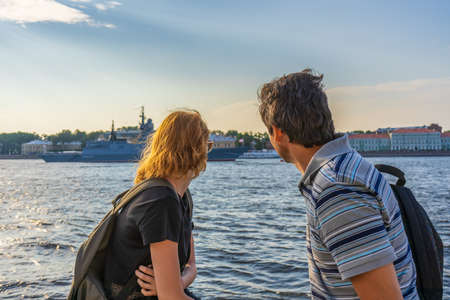 Foto de Middle-aged dark-haired man and young redhead lady on Neva river embankment looking at warships and architectural ensemble in summer evening at sunset. Travel concept. Saint Petersburg, Russia. - Imagen libre de derechos