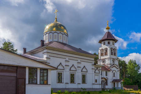 Foto de Church to St. Grand Prince Alexander Nevsky in Pudozh after restoration. Orthodox temple and bell tower against northern pine forest and blue sky in summer sunny day. Karelia, Russia. - Imagen libre de derechos
