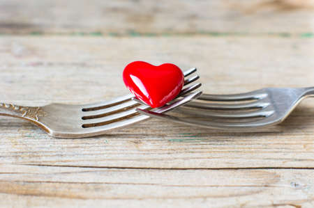Photo pour Red heart between two vintage forks on rustic wooden background - image libre de droit