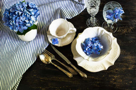 Vintage style table setting with fresh blue hydrangea flowers on rustic wooden table