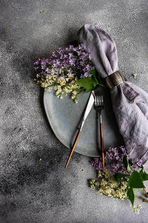 Foto de Spring table setting with beautiful lilac flowers on grey concrete background with copy space - Imagen libre de derechos