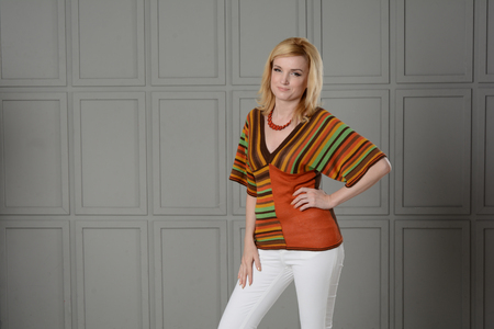 Foto de Women posing in studio. She is dressed in a striped knitted blouse and white jeans. She has a necklace on her neck. Clothing in the style of the 1970s. One hand at the waist. Unusual background. - Imagen libre de derechos
