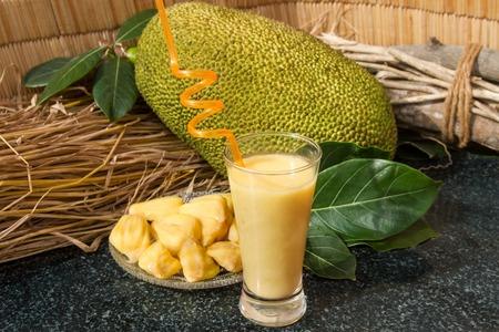 Foto de Jackfruit juice in a glass. Fresh sweet jackfruit slices on a glass plate. Exotic ripe jackfruit ready for eat. Sweet jackfruit cocktail. Organic fruit concept. Tropical fruit. Selective focus. - Imagen libre de derechos