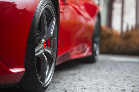 Detail of red super sport car front side with focus on wheel tire