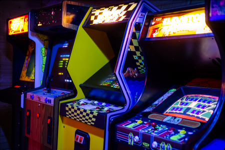 Photo for Row of Old Arcade Video Games with Shining Displays in a Dark Gaming Room - Royalty Free Image