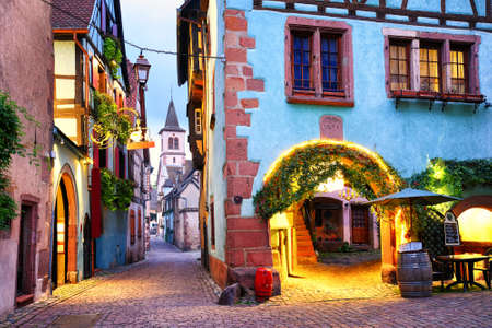 Photo for Picturesque street with traditional colorful houses in Riquewihr village on alsatian wine route, Alsace, France - Royalty Free Image