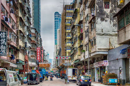 Busy street with advertising signs and buses in Kowloon Peninsula district in Hong Kong. The City is known worldwide for its colorful signs.