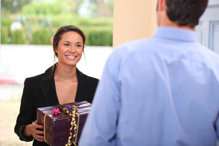 Photo for Woman at a front door with a gift - Royalty Free Image