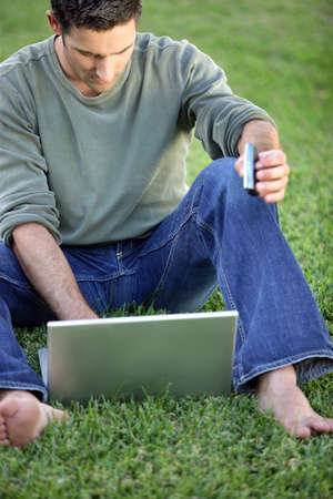Man sat barefoot in filed with laptop