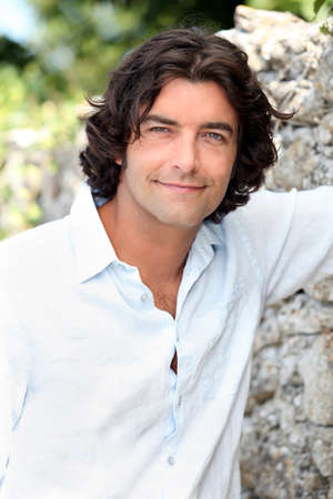 Photo for Handsome man with long hair standing by an old stone wall - Royalty Free Image