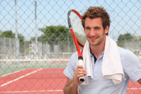Photo for A tennis player posing in front of a tennis court with his racket. - Royalty Free Image