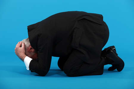 Businessman huddled on the floor