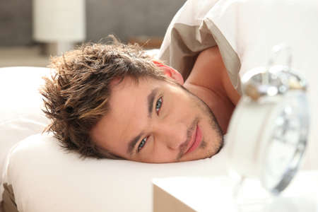 Photo for young man in bed waking up - Royalty Free Image