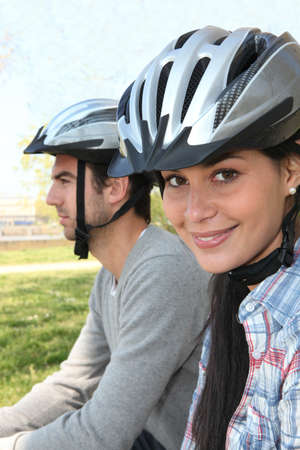 Young couple wearing cycle helmets
