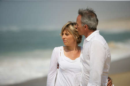 Photo pour Married couple dressed in white taking a walk along the beach - image libre de droit