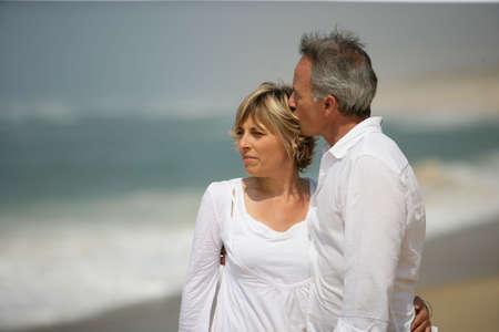 Foto de Married couple dressed in white taking a walk along the beach - Imagen libre de derechos