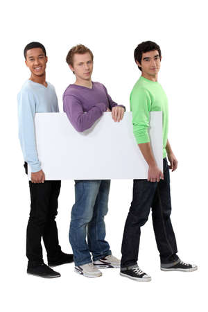 Three young men carrying a blank board