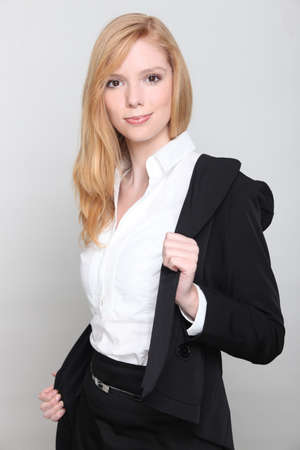 Blond businesswoman removing jacket