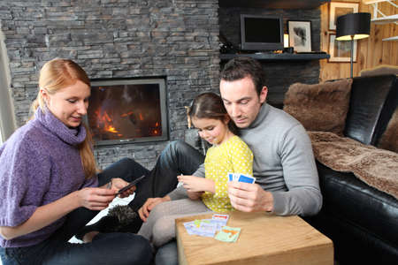 Family gathered by the fire place playing cards