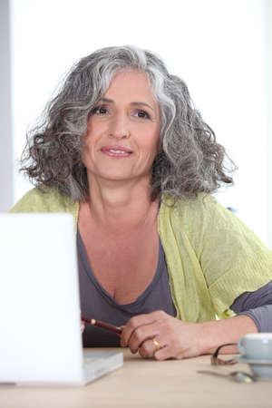Gray-haired woman in front of laptop computer