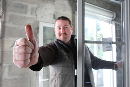 Photo pour Man fitting a window giving you the thumbs up - image libre de droit