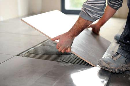 Photo pour Man laying floor tiles - image libre de droit