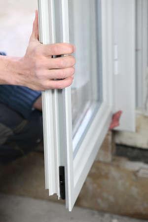 Photo pour Man installing double glazed windows - image libre de droit