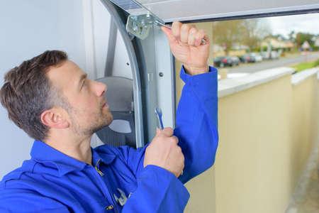 Photo pour Man installing a garage door - image libre de droit