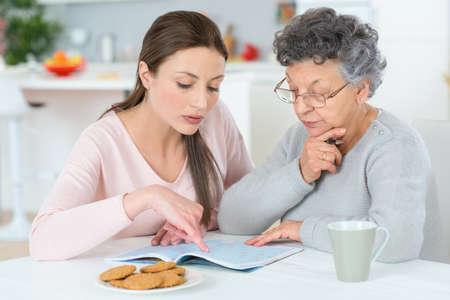 Foto de Helping her grandma do a crossword - Imagen libre de derechos
