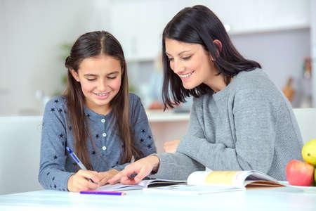 Foto de Mom helping her daughter do her homework - Imagen libre de derechos