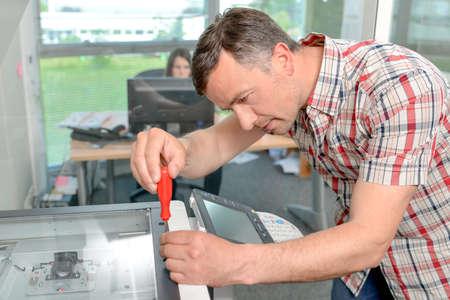 Foto de Handyman fixing the office printer - Imagen libre de derechos