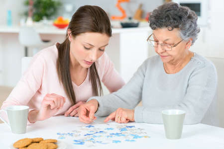 Photo pour Old lady doing a jigsaw puzzle - image libre de droit