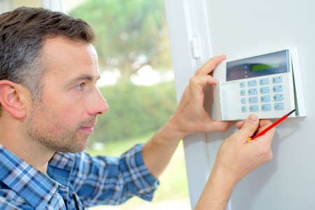 Photo pour Electrician fitting an intrusion alarm - image libre de droit